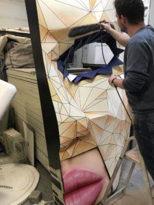 Domalowywanie brwi na standzie w kształcie maski z twarzą kobiety wykonanej z włókna szklanego